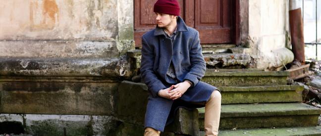 Mann als Absoluter Beginner sitzt unglücklich auf Treppe vorm Haus