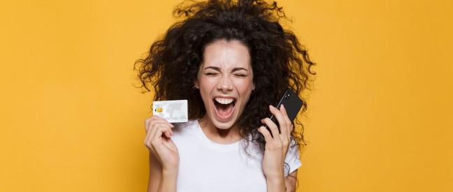 Frau mit Smartphone und Kreditkarte schreit lachend