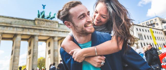 Frau umarmt Mann beim Date in Berlin am Brandenburger Tor