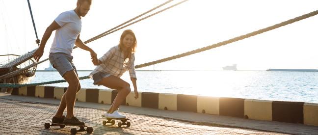 Paar Händchen haltend beim Skateboard fahren