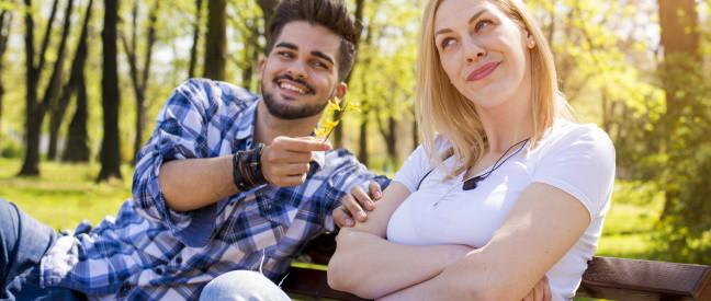 Mann und Frau sitzen auf Parkbank und flirten