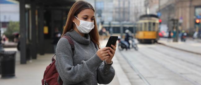 Frau mit Schutzmaske schaut an der Bahnhaltestelle aufs Handy