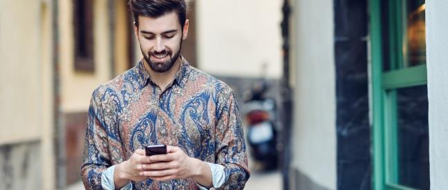 Mann mit Smartphone flirtet unterwegs auf Tinder
