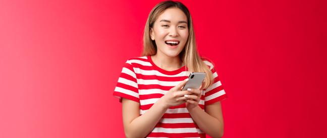 Frau mit Handy lacht über guten Tinder-Opener