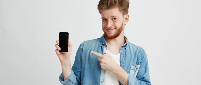 Mann mit Handy freut sich über Tinder Platin