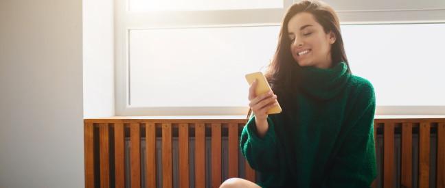 Frau mit Smartphone nutzt Dating-App